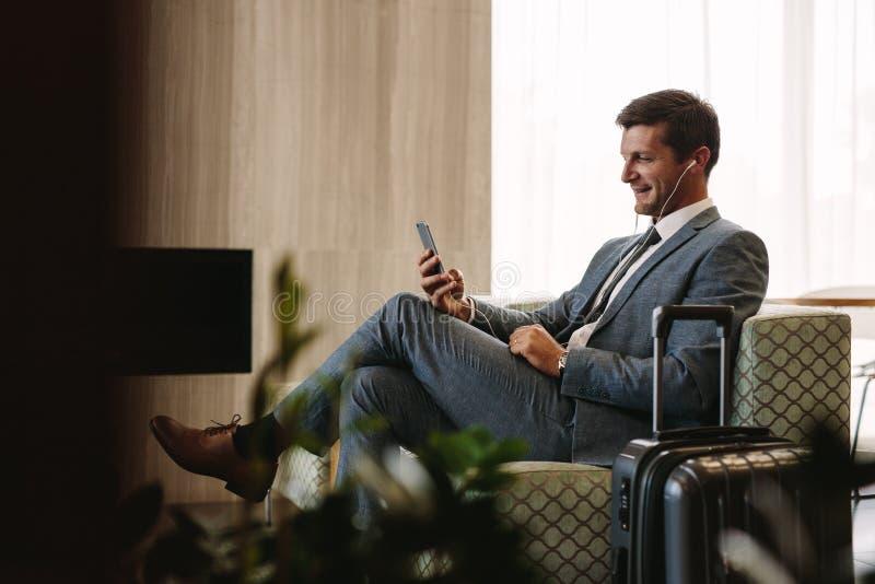Executivo empresarial que faz uma chamada video na sala de estar do aeroporto imagem de stock royalty free