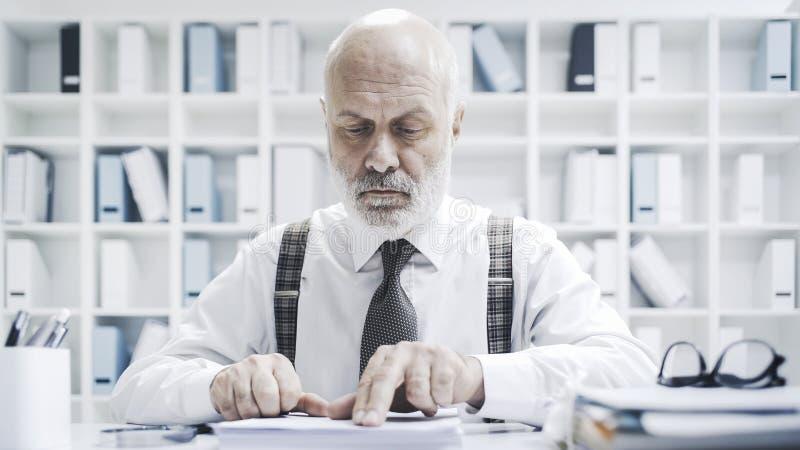 Executivo empresarial que verifica o documento imagens de stock royalty free