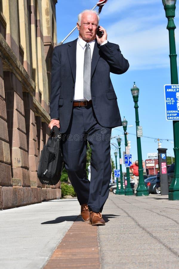 Executivo empresarial superior adulto que usa o telefone celular e o passeio infeliz imagem de stock