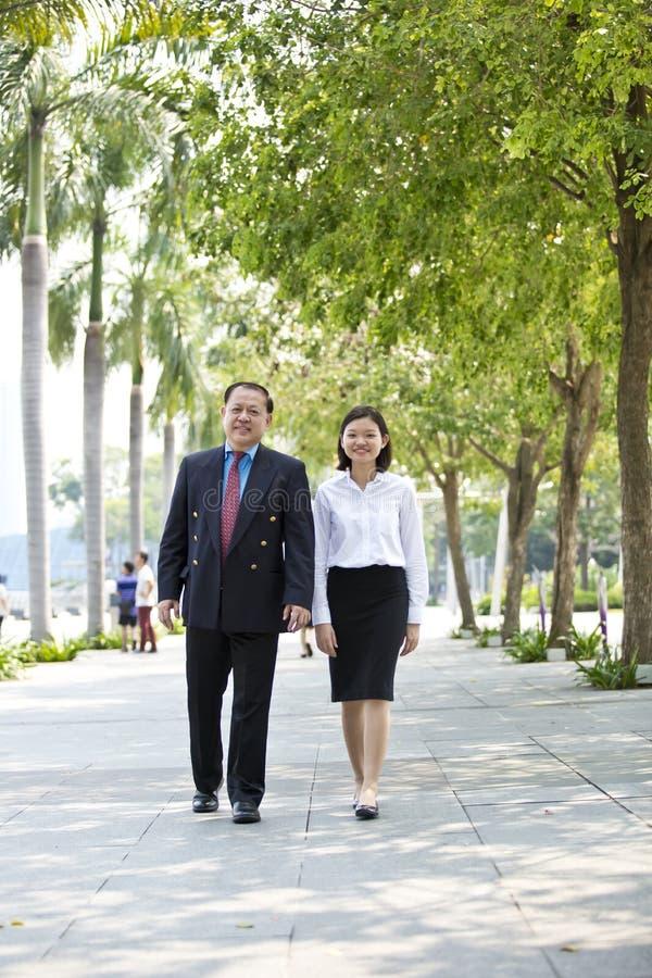 Executivo fêmea asiático novo e homem de negócios superior que andam junto fotografia de stock
