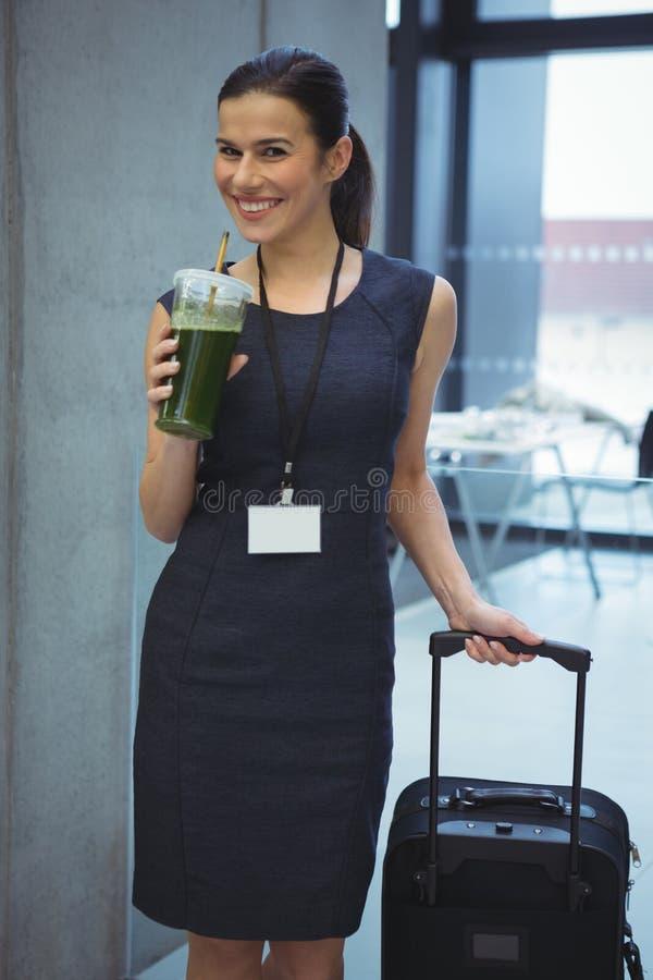 Executivo fêmea bonito que está com bagagem ao comer o suco no corredor fotos de stock