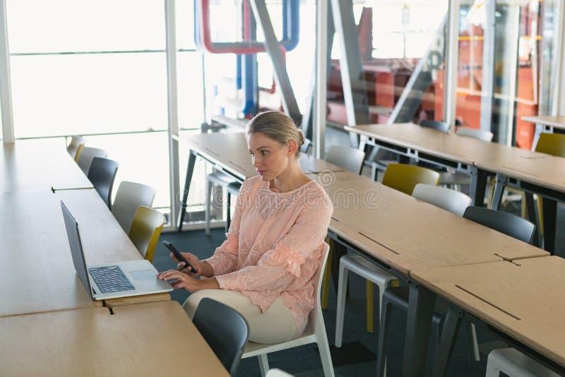 Executivo fêmea que usa o portátil ao guardar o telefone celular na sala de conferências foto de stock royalty free