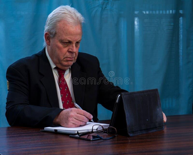 Executivo idoso na tabela da sala de reuniões imagem de stock