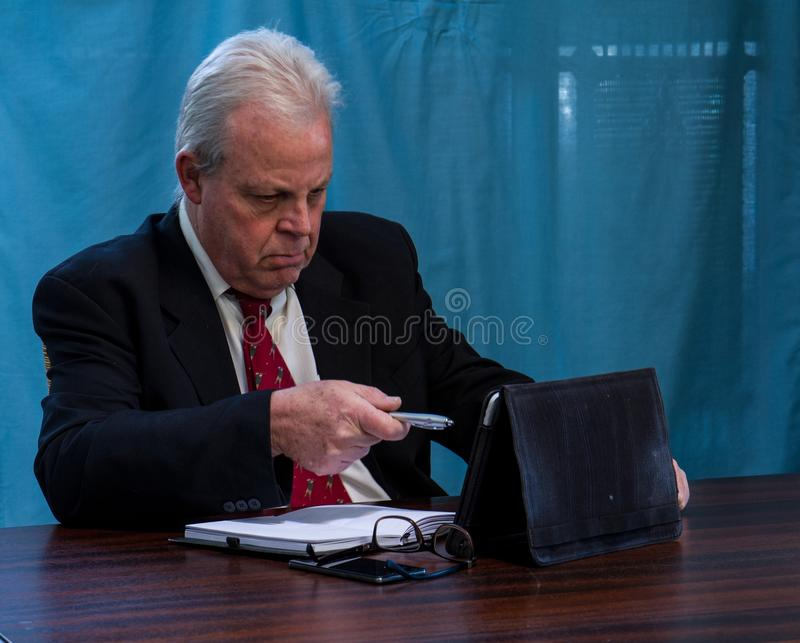 Executivo idoso na tabela da sala de reuniões fotografia de stock