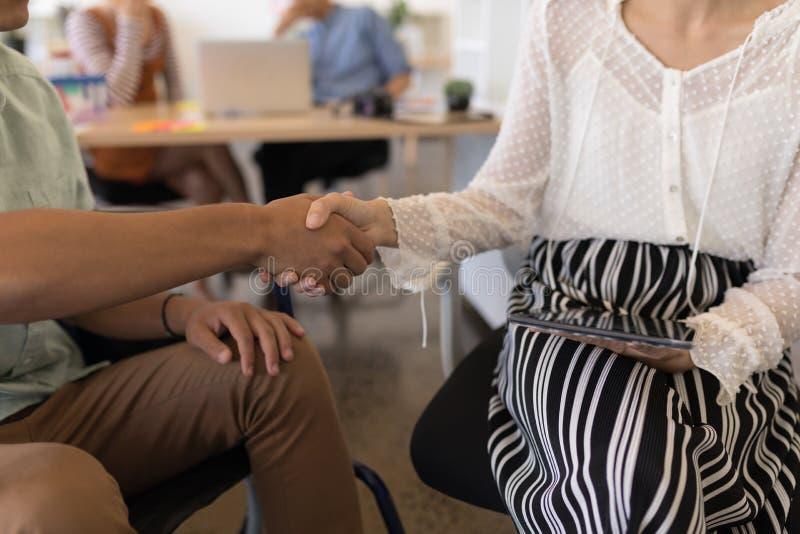 Executivo masculino deficiente que agita a mão com seu colega de trabalho no escritório foto de stock royalty free