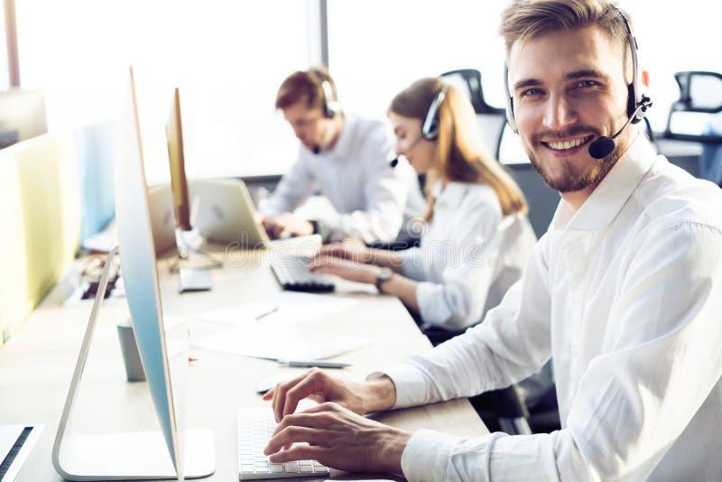 Executivo masculino novo feliz do apoio ao cliente que trabalha no escrit?rio imagens de stock