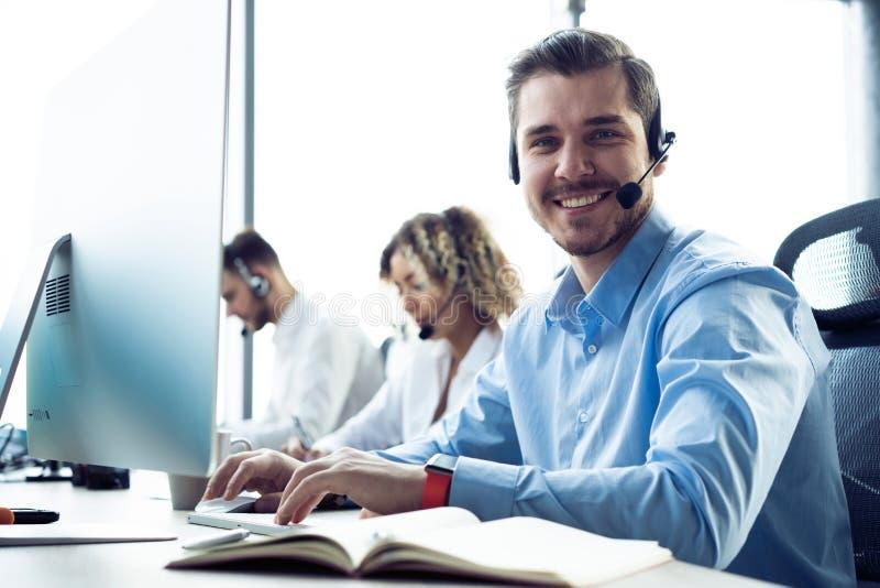 Executivo masculino novo feliz do apoio ao cliente que trabalha no escrit?rio imagens de stock royalty free