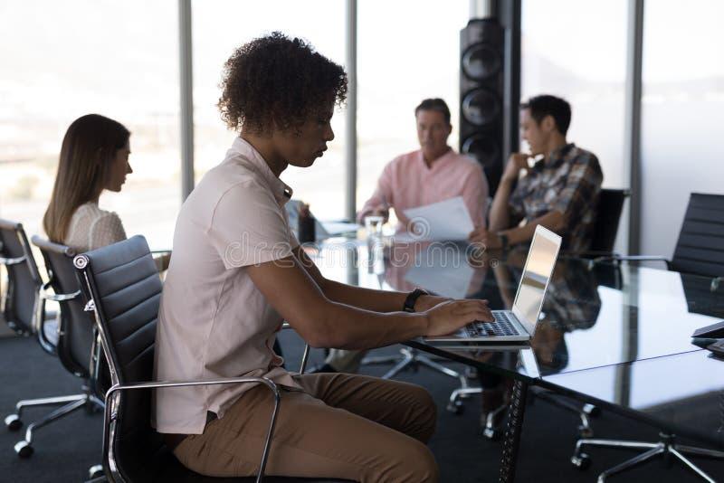 Executivo masculino novo que trabalha no portátil no escritório imagens de stock royalty free