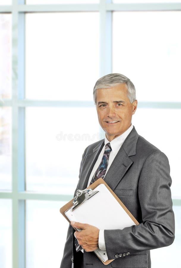 Executivo masculino sênior de sorriso com prancheta fotos de stock royalty free