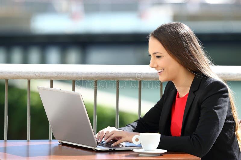 Executivo que datilografa em um portátil em uma cafetaria imagem de stock