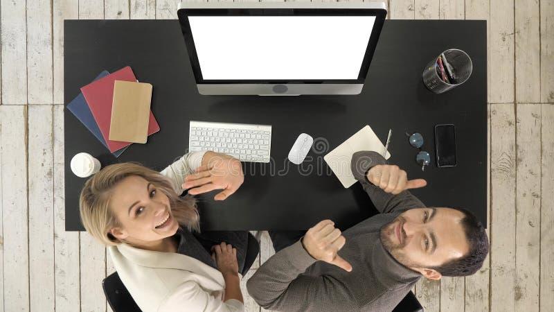 Executivos alegres que olham à câmera e que falam no escritório Indicador branco imagens de stock royalty free