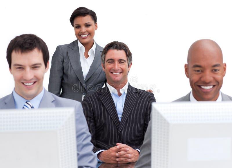 Executivos alegres que trabalham em computadores fotos de stock royalty free