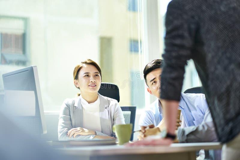 Executivos asiáticos novos que encontram-se no escritório fotos de stock