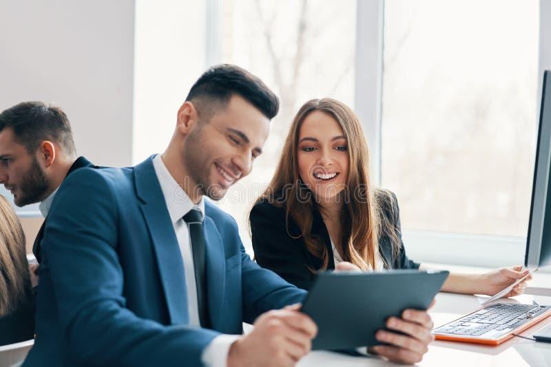 Executivos bem sucedidos de sorriso que discutem ideias usando a tabuleta digital no escritório imagens de stock royalty free