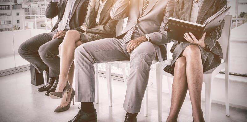 Executivos bem vestidos que esperam para ser chamado para a entrevista ilustração royalty free
