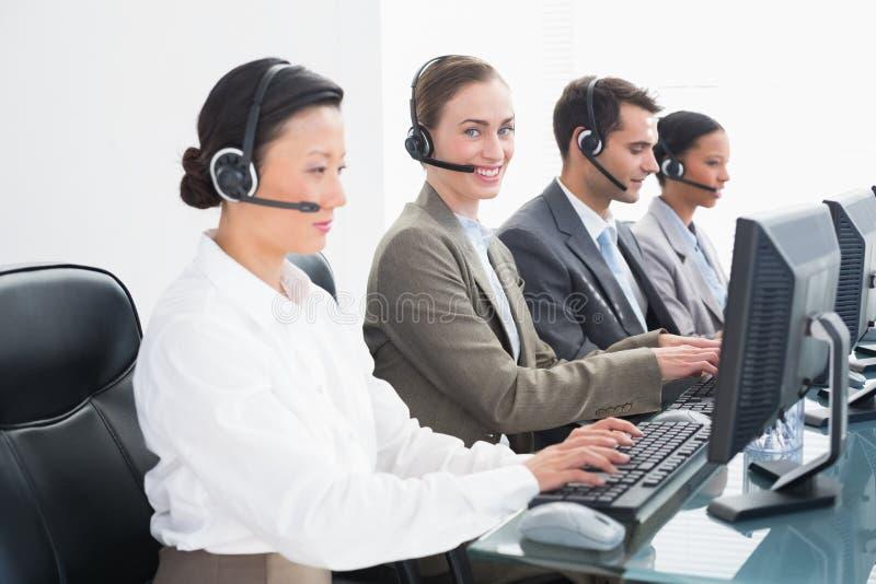 Executivos com auriculares usando computadores imagem de stock royalty free