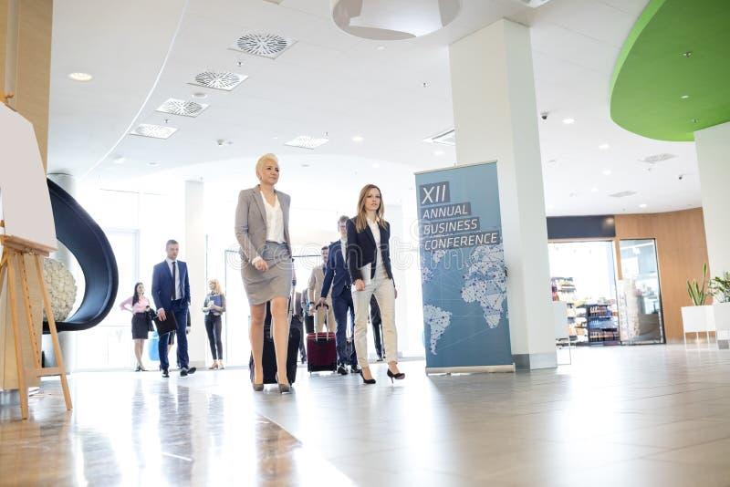 Executivos com bagagem que andam no centro de convenções imagens de stock royalty free