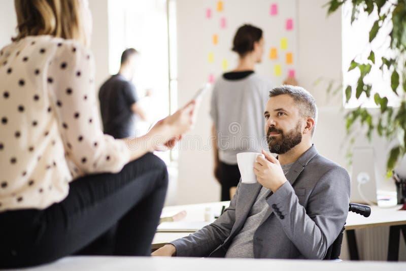 Executivos com a cadeira de rodas no escritório imagens de stock royalty free