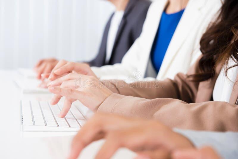 Executivos das mãos que datilografam em teclados de computador imagens de stock