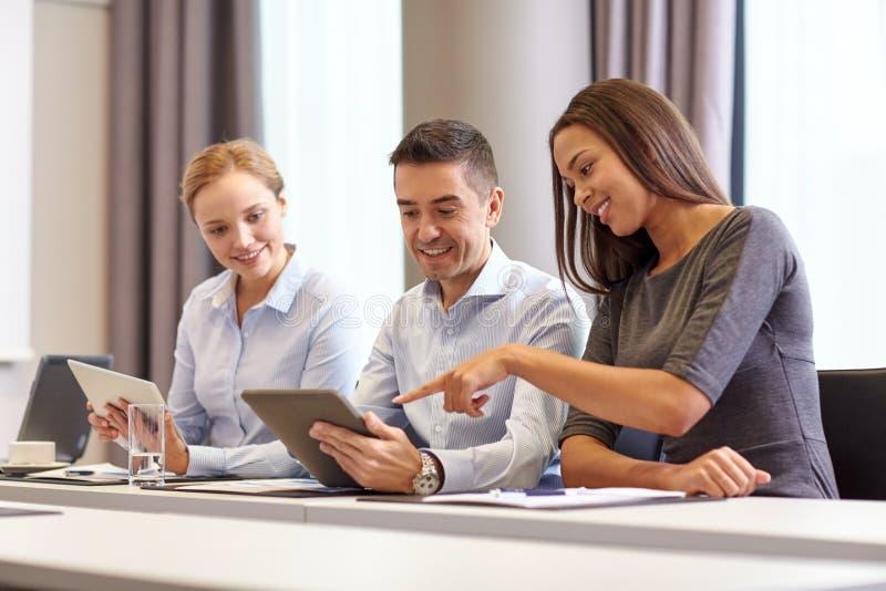 Executivos de sorriso com o PC da tabuleta no escritório fotografia de stock