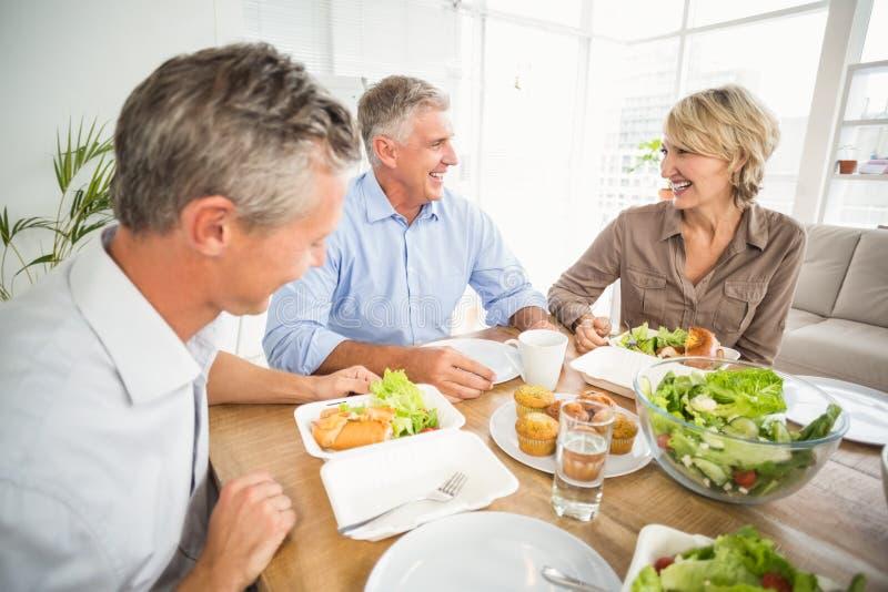 Executivos de sorriso que têm o almoço junto imagens de stock