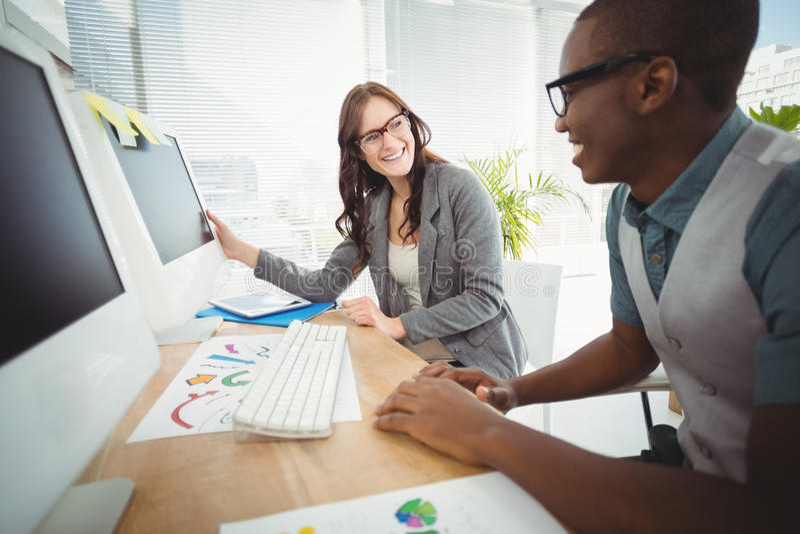 Executivos de sorriso que vestem os monóculos que trabalham na mesa do computador fotos de stock royalty free