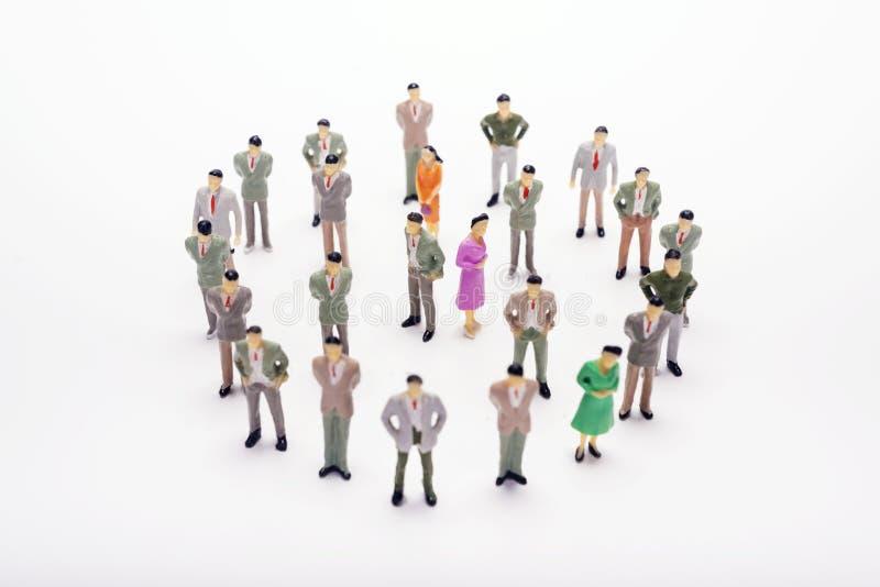 Executivos diminutos que estão no círculo sobre o contexto imagens de stock