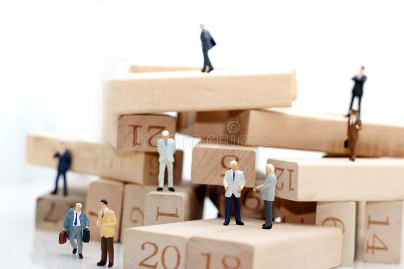 Executivos diminutos que sentam-se no bloco de madeira, recrutamento e fotos de stock royalty free