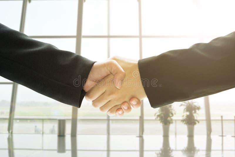 Executivos do aperto de mão no fundo do escritório, negócio do conceito foto de stock royalty free