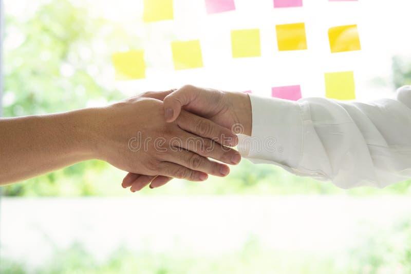 Executivos do close up que agitam as mãos, terminando acima uma reunião foto de stock royalty free