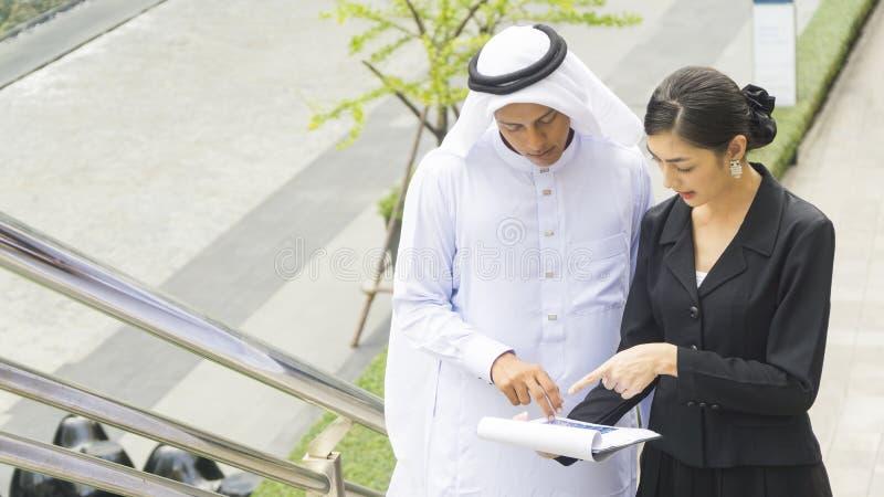 Executivos do homem árabe e a conversa e o presente da mulher fotografia de stock royalty free