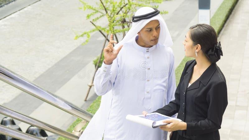 Executivos do homem árabe e a conversa e o presente da mulher fotografia de stock