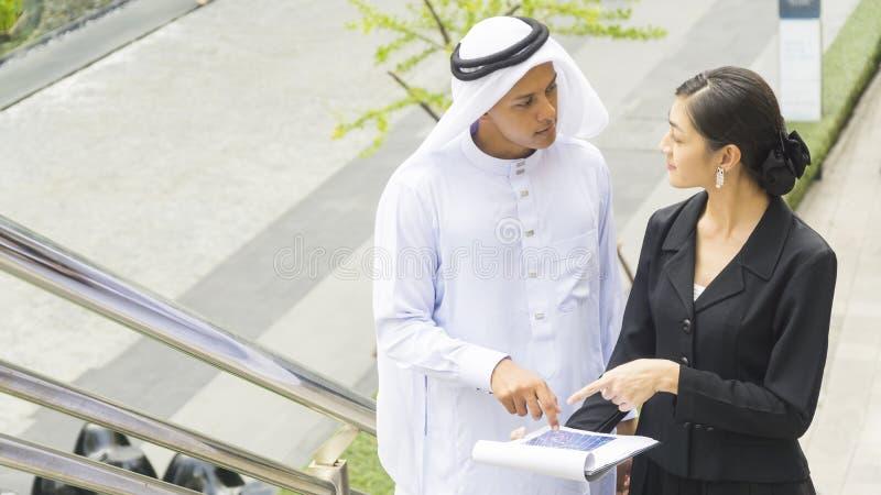 Executivos do homem árabe e a conversa e o presente da mulher imagens de stock royalty free
