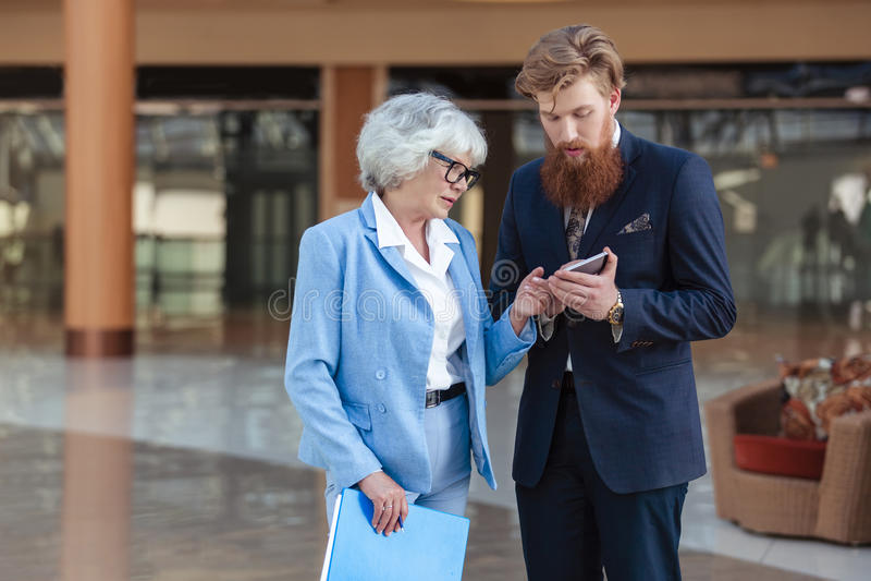 Executivos do olhar no smartphone imagem de stock royalty free