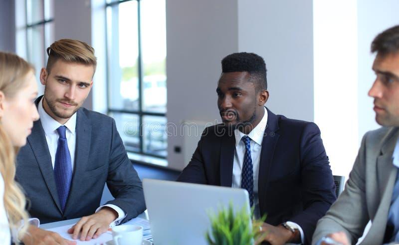 Executivos em discutir algo ao sentar-se junto na tabela fotografia de stock royalty free