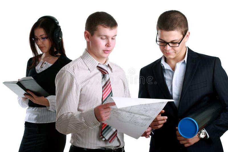 Executivos em ternos de negócio que discutem a planta imagem de stock