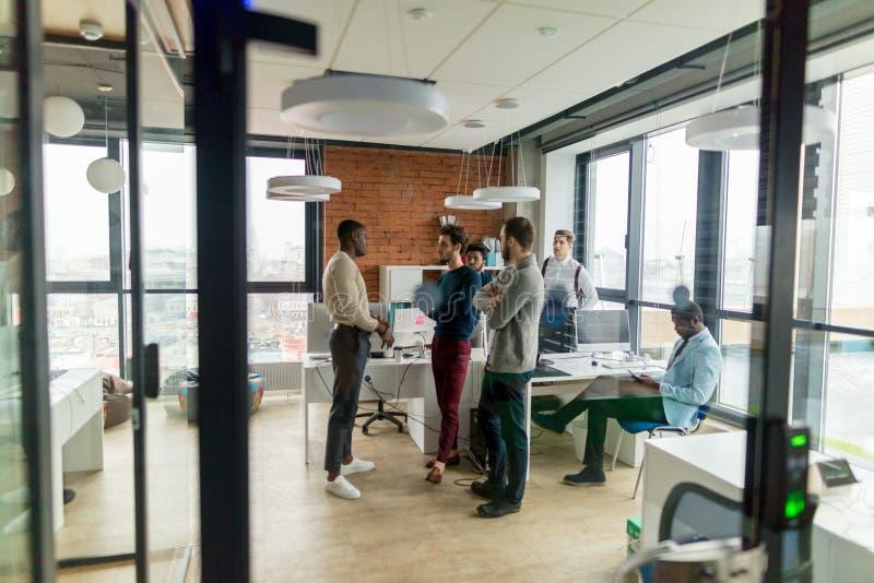 Executivos em um escritório do espaço aberto com uma janela panorâmico, possibilidade remota fotos de stock