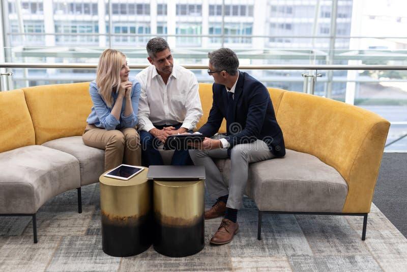 Executivos empresariais dos Caucasians que interagem um com o otro no sofá fotografia de stock royalty free