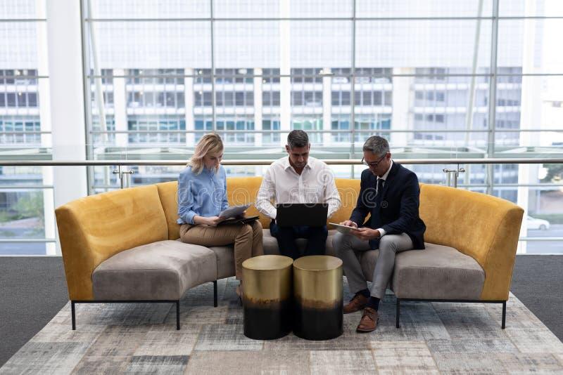 Executivos empresariais dos Caucasians que trabalham no sofá imagem de stock royalty free