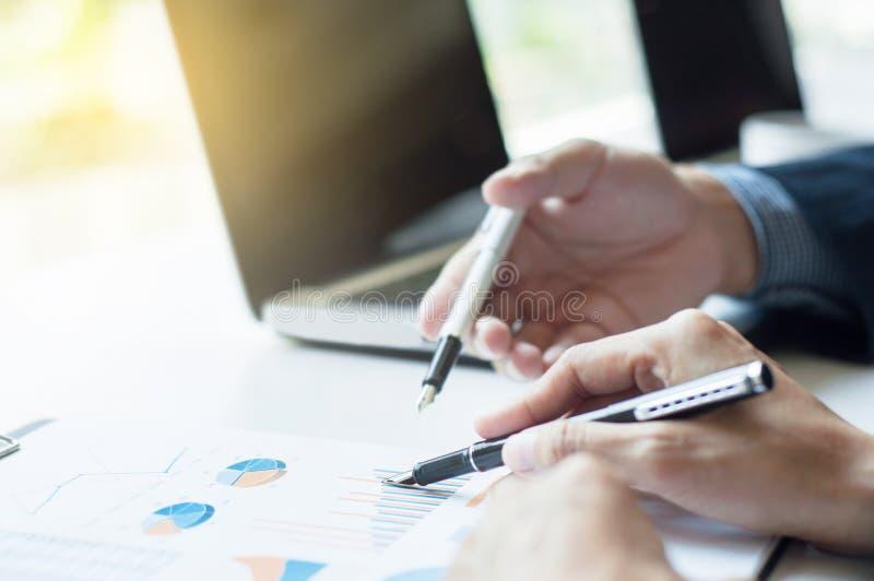 Executivos empresariais que discutem em dados com o fundo do portátil imagem de stock