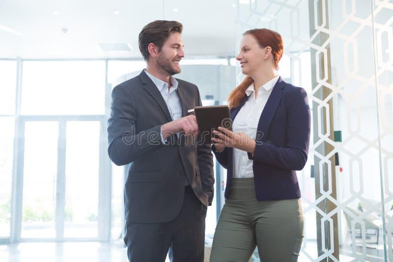 Executivos empresariais que discutem sobre a tabuleta digital imagem de stock