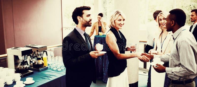Executivos empresariais que interagem um com o otro ao comer o café fotografia de stock