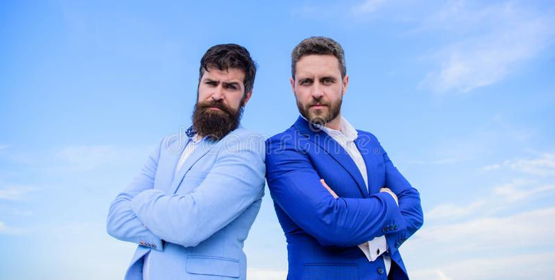 Executivos farpados que levantam seguramente Os homens de negócio estão o fundo do céu azul Aperfeiçoe em cada detalhe poço imagens de stock royalty free
