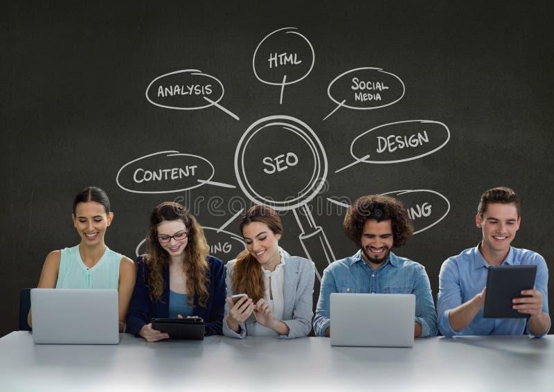 Executivos felizes em uma mesa que olha telefones, computadores e tabuletas contra wi verdes do fundo fotos de stock
