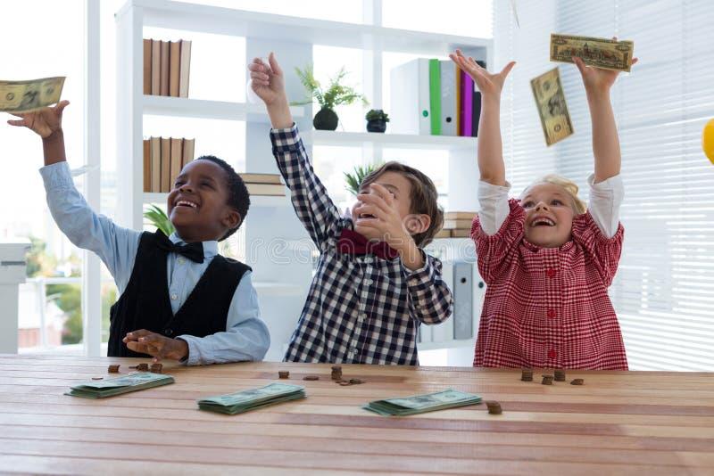 executivos felizes que jogam o dinheiro no ar no escritório fotos de stock royalty free