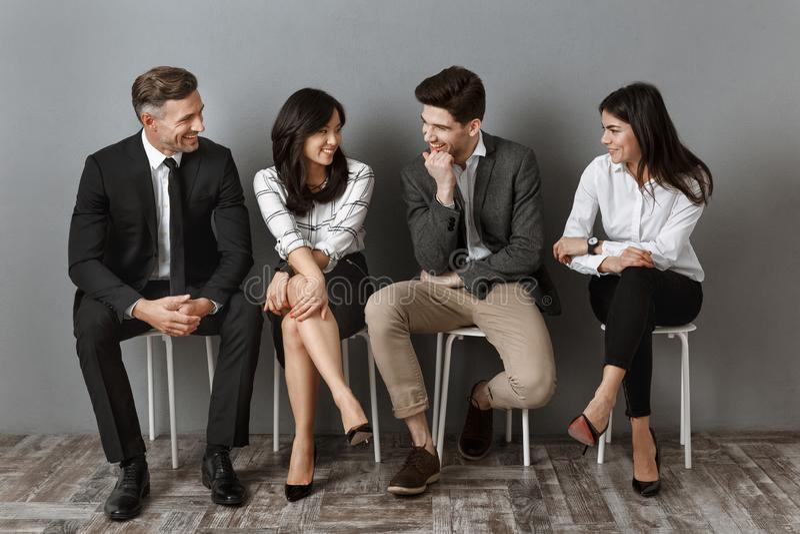 executivos inter-raciais no vestuário formal que tem a conversação ao esperar fotos de stock
