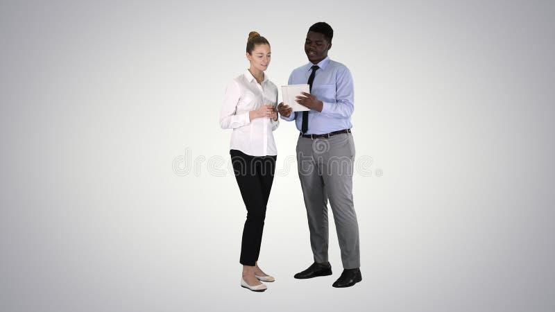 Executivos modernos que trabalham em uma tabuleta no fundo do inclinação imagem de stock