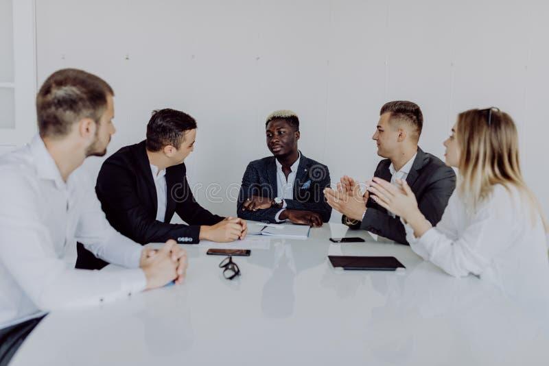 Executivos multirraciais que aplaudem o assento na tabela de conferência, mãos de aplauso da equipe diversa após a reunião de gru fotos de stock royalty free