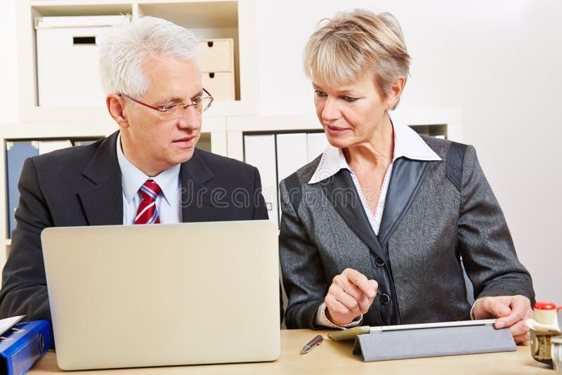 Executivos na comparação do escritório fotografia de stock
