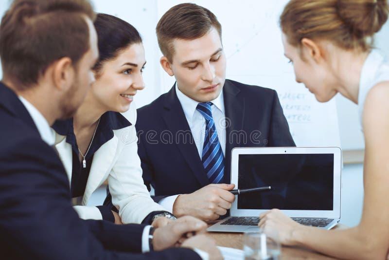 Executivos na reunião no escritório Focalize na mulher que aponta no portátil fotografia de stock royalty free